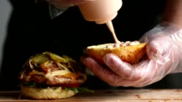 The process of cooking big Burger is a professional chef, close-up. Smear the bun with the sauce and assemble the Burger