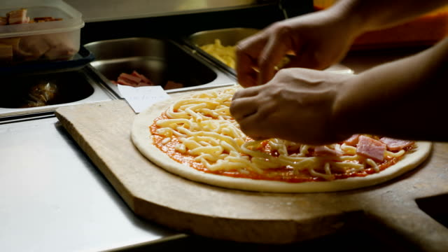 The process of making pizza at kitchen, Chef's hands putting the ingredients for the pizza