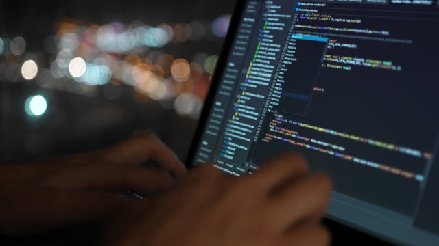 vídeos de stock e filmes b-roll de the programmer writes the code for the development of the website, against the background of a beautiful night window in which the city lights are visible in defocus. - codificar