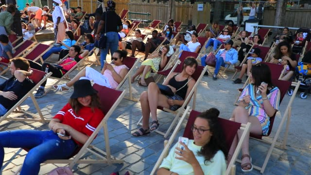 """the public wait in the lounge chairs for the start of the film during paris plages launch of """"le cinema sur l'eau"""" with the screening of """"le grand... - laziness stock videos & royalty-free footage"""