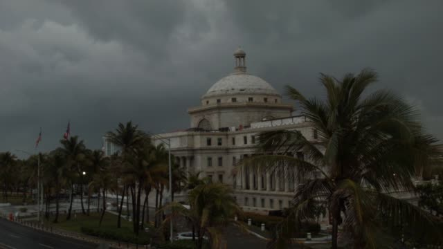 the puerto rican flag flies near the capitol building as the island's residents deal with the government's $72 billion debt on july 1, 2015 in san... - puerto rican ethnicity stock videos & royalty-free footage
