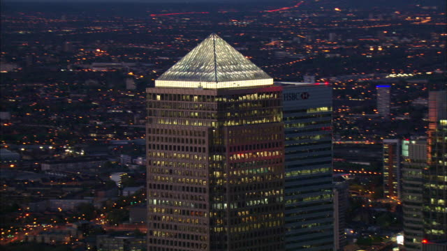 the pyramid dome of one canada square glows in the canary wharf business district of london's isle of dogs. - canary wharf stock videos & royalty-free footage