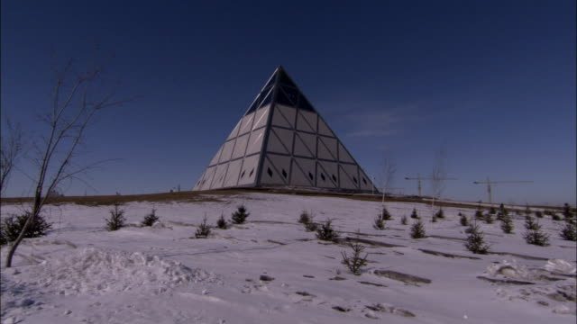 The Pyramid of Peace sits in a snowy field, displaying triangles and diamonds on its paneled sides.