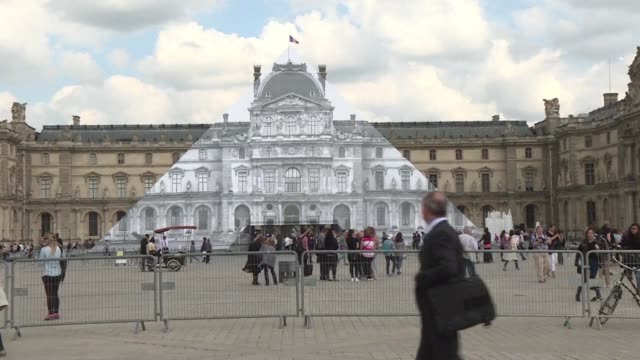 the pyramid of the louvre museum in paris has been covered by a trompel'oeil art installation created by french photographer jr - oeil stock videos and b-roll footage