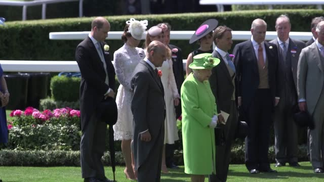 The Queen and Duke of Edinburgh among members of the Royal family bowing their heads as they observe a minute of silence in the Parade Ground at...