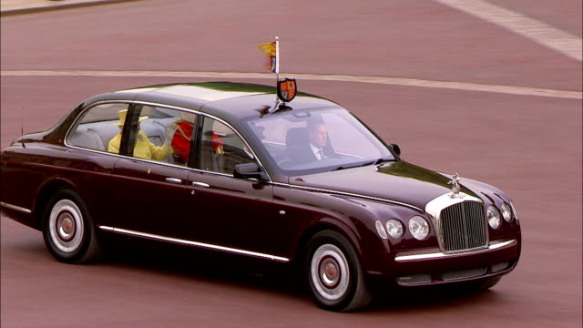 the queen and prince philip leave buckingham palace in a royal limousine moving past cheering crowds as they head to westminster abbey available in hd - バッキンガム宮殿点の映像素材/bロール
