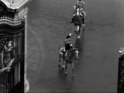 The Queen and the Duke of Edinburgh stop their horses at the gates of Buckingham Palace to watch the passing Grenadier Guards during the Trooping the...