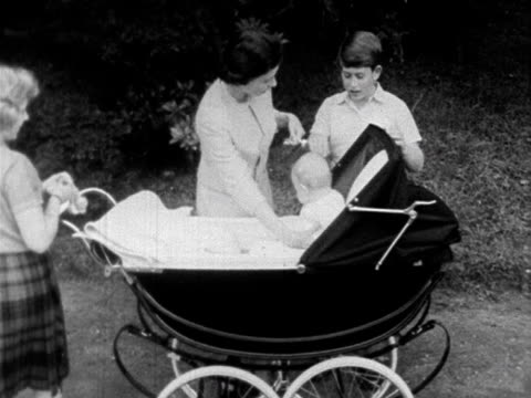 The Queen lifts baby Prince Andrew out of his pram as Princess Anne Prince Charles and Prince Philip stand next to her 1960