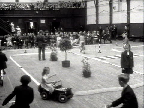 the queen mother and princess margaret watch children taking part in a road safety demonstration in a school hall in king's lynn - princess margaret 1950 stock videos and b-roll footage