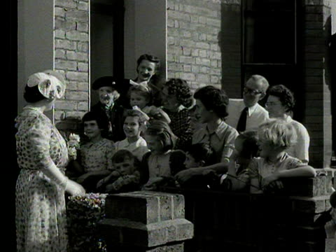 the queen mother leaves a terraced house and chats to some of the spectators during her tour of suburban gardens in fulham 1954 - queen dowager stock videos and b-roll footage