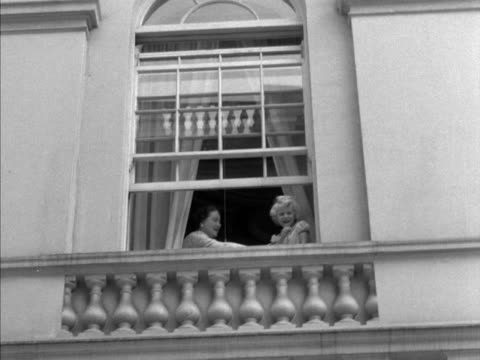 the queen mother, prince charles and princess anne wave from a window at clarence house during her 55th birthday celebrations. - エリザベス・ボーズ=ライアン点の映像素材/bロール