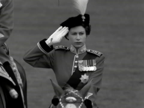 the queen on horseback and wearing her colonel-in-chief uniform salutes during the trooping the colour ceremony outside buckingham palace. 1953. - 軍旗分列行進式点の映像素材/bロール