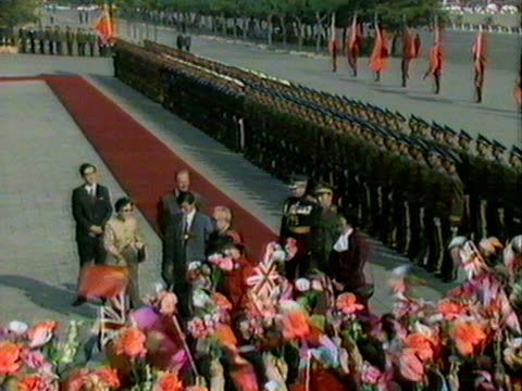the queen prince philip and president li xiannian walk past a group of people waving flags and paper flowers during the queen's visit to beijing.... - peerage title stock videos & royalty-free footage