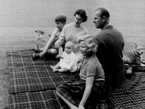 the queen prince philip prince charles princess anne and a baby prince andrew sit on a rug in the balmoral grounds 1960 - ヨーク公 アンドルー王子点の映像素材/bロール