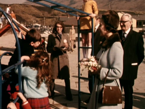 the queen smiles at children who are playing outside the new community centre in the village of aberfan. march 1973. - 屋外遊具点の映像素材/bロール
