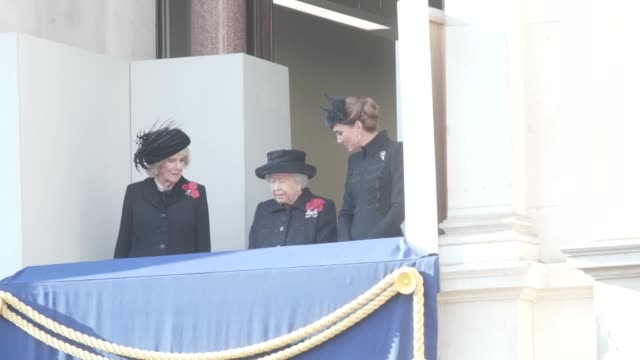 vídeos de stock, filmes e b-roll de the queen stands with the duchess of cornwall and duchess of cambridge on a balcony in whitehall as the royals watch the remembrance ceremony. the... - dia do armistício britânico