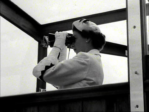the queen uses a pair of binoculars to observe the royal naval fleet assembled at spithead 1953 - elizabeth ii stock videos & royalty-free footage