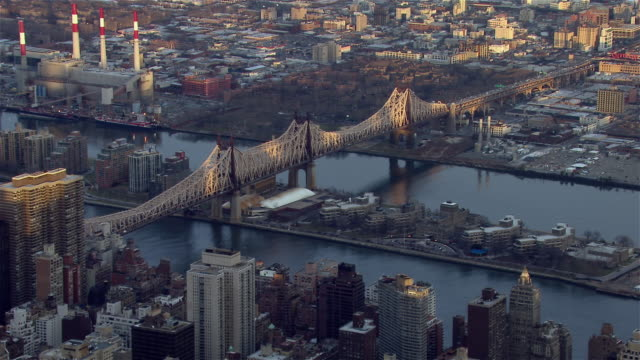 the queensboro bridge crosses over the east river and roosevelt island between manhattan and queens in new york city. - queens stock-videos und b-roll-filmmaterial