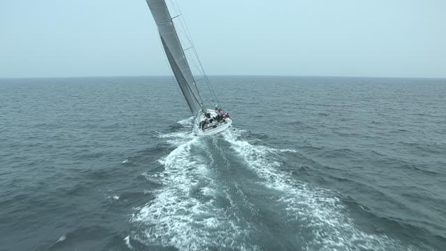 the racing yacht, rambler 100 cruises toward the horizon. - barca a vela video stock e b–roll