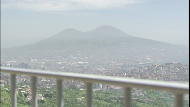 The railing of a villa frames a view of Mt. Vesuvius and the city of Naples, Italy.