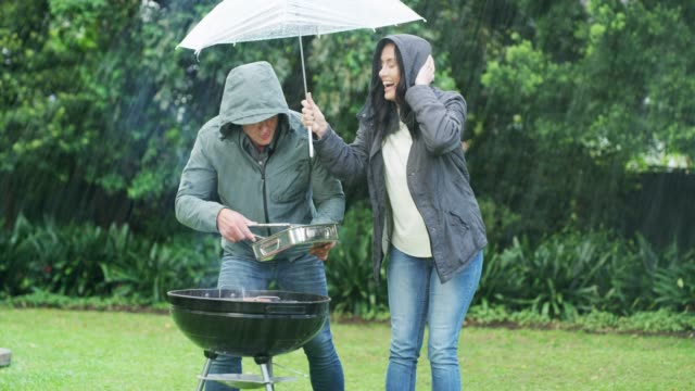 the rain won't stop their barbecue - mature couple stock videos & royalty-free footage