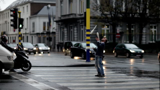 The rainy autumn evening in Brussels The street juggler entertains drivers at the crossroads NO