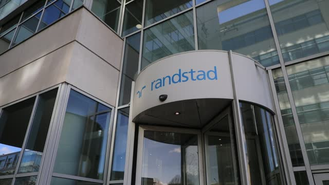 the randstad company logo at the entrance to the french headquarters on december 4 in saint-denis, france. dutch multinational human resource... - クラシファイド広告点の映像素材/bロール