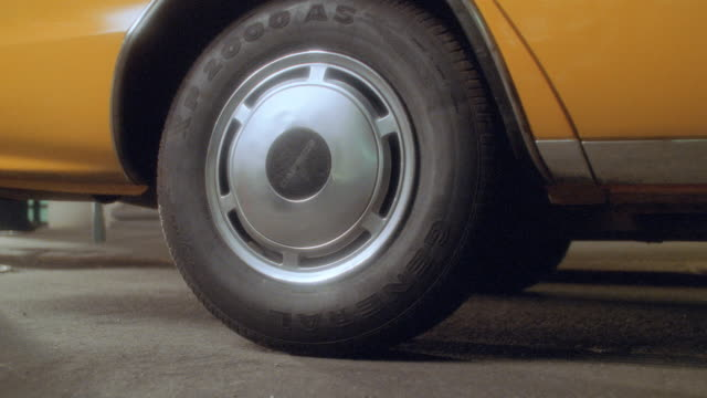 the rear wheel of a taxicab spins and smokes as the taxi speeds away. - yellow taxi stock videos & royalty-free footage