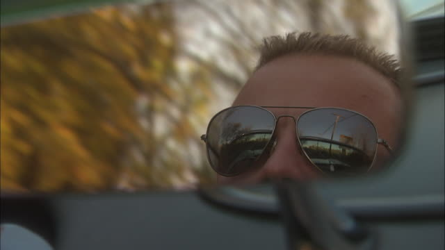 the rear-view mirror of a convertible reflects a driver's face. - sunglasses stock videos & royalty-free footage