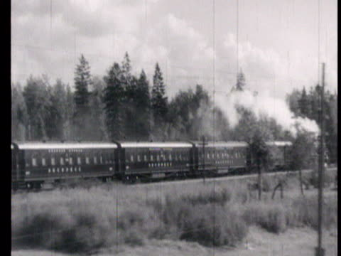 vídeos de stock, filmes e b-roll de the red arrow moscow-leningrad railway in 1951 express train and steam engine running again along industrialized region, countryside and seashore /... - 1951