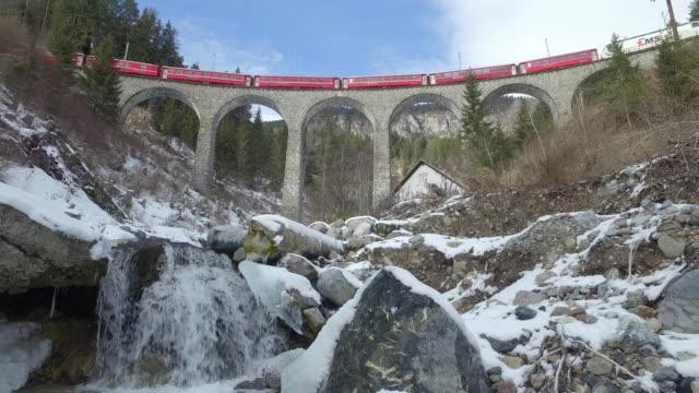 The red Bernina Express train passing over the Landwasser Viaduct. Switzerland.