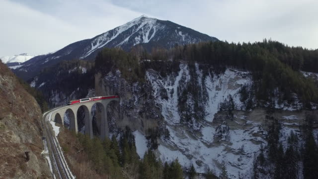 The red Bernina Express train passing over the Landwasser Viaduct. Switzerland.