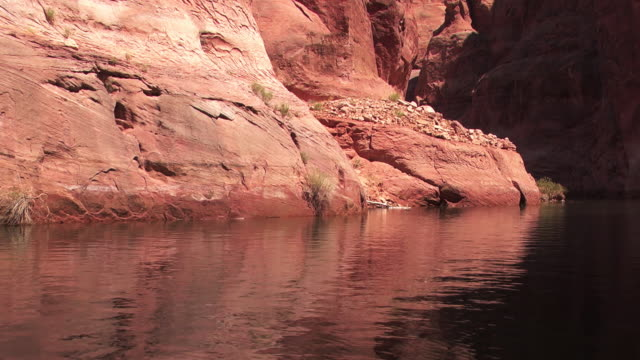 the red cliffs of a canyon cast reflections on the surface of a river. - black canyon stock videos & royalty-free footage