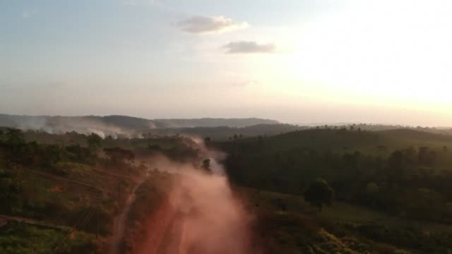 the red dust of the br230 highway nicknamed the transamazonica mixes with fires at sunset in brazil's para state - sunset stock videos & royalty-free footage