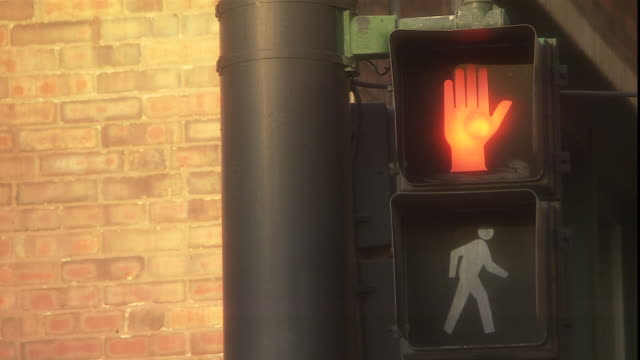 the red hand on a pedestrian crossing sign flashes and then glows steadily. - warning sign stock videos & royalty-free footage