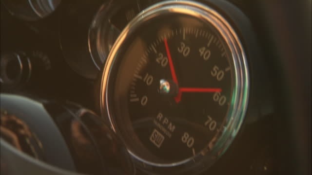 the red hands on an rpm gauge of a classic convertible move as the engine is revved. - gauge stock videos & royalty-free footage