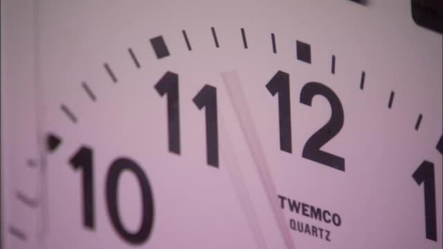 vídeos de stock e filmes b-roll de the red second hand of a twemco quartz clock stutters past the numeral 12. - quartzo