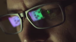 The reflection at the glasses of man: looking a site (side view)