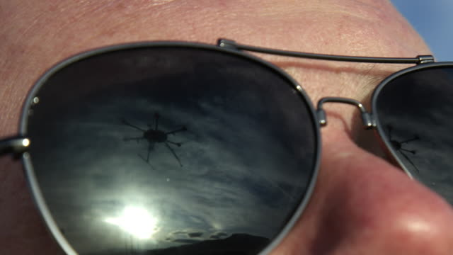 the reflection of a hexacopter drone flying in a close-up shot of a caucasian man's dark sunglasses - surveillance stock videos & royalty-free footage
