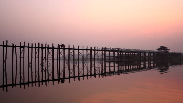 the reflection of a wooden bridge in the water in mandalay - romantische stimmung stock-videos und b-roll-filmmaterial