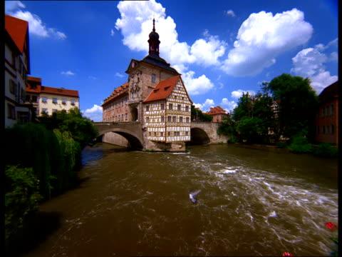 the regnitz river flows on both sides of the altes rathaus in bamberg, germany. - rathaus bildbanksvideor och videomaterial från bakom kulisserna