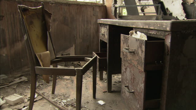 the remains of a desk and chair occupy a room in an abandoned building. - run down stock videos & royalty-free footage