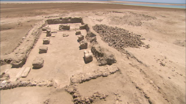 the remains of an ancient temple break the monotony of desert sand. - old ruin stock videos & royalty-free footage