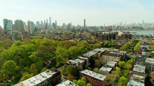 the remote aerial view toward the manhattan downtown financial district from brooklyn, over the residential district and the fort green park - manhattan new york city stock videos & royalty-free footage