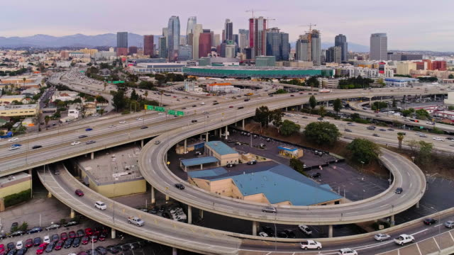 the remote scenic aerial view of downtown los angeles from west washington boulevard, over the huge overpass crossing between santa monica freeway and harbor freeway and transit way - american interstate stock videos & royalty-free footage