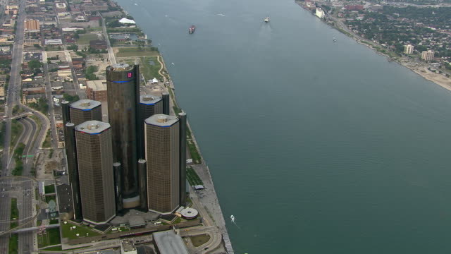 the renaissance center complex overlooks the detroit river in this aerial shot of downtown detroit. - detroit river stock-videos und b-roll-filmmaterial