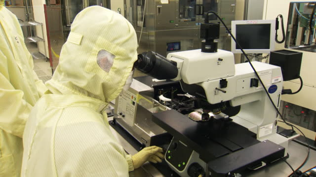 the researcher looking at microscope at the laboratory - microscopio video stock e b–roll