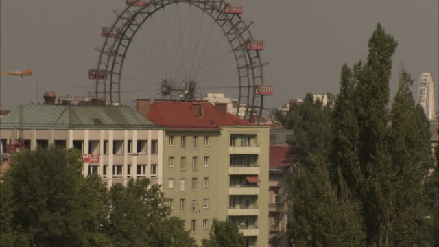 the riesenrad ferris wheel slowly turns in prater amusement park as a ferry moves along a river in vienna, austria. available in hd - prater park stock videos & royalty-free footage