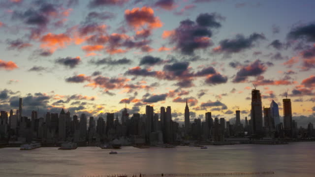 the rising sun adds pops of color to the clouds above a silhouetted manhattan skyline along the hudson river. - manhattan new york city stock videos & royalty-free footage