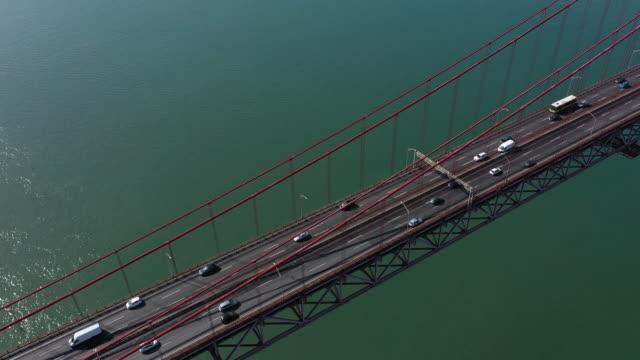vídeos de stock e filmes b-roll de the river tagus and traffic on the bridge - ponte